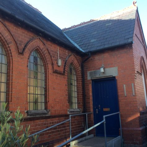 Willaston (Wirral) PM chapel  1889: side entrance (originally the main door) to the vestibule, chapel (left) and 'classroom' (right).  Note the art nouveau fleur-de-lys | Christopher Wells September 2020