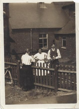 An unusual view of the back of the School room, soon after it was built in 1914. The people in the photo may be the caretakers who lived in the Chapel Cottage next door. This would be the side of the fence in the foreground.